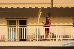 Woman Standing on the Balcony Early in the Morning During the Su. Nrise and Drinking Coffee or Tea From the Cup or Mug Royalty Free Stock Photography