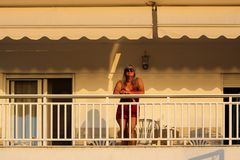 Woman Standing on the Balcony Early in the Morning During the Su. Nrise Royalty Free Stock Photography