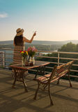 Woman Standing at Balcony. Woman in Hat with Paper Airplane on Balcony royalty free stock images