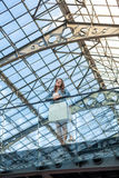 Woman standing on balcony at railway station with glass ceiling Stock Image