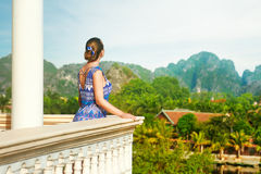 Woman standing on the balcony watching beautiful mountains view. Royalty Free Stock Photo