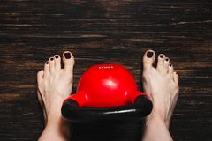 Woman standing bare foot with red kettlebell between her legs Stock Photos
