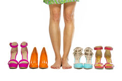 Woman is standing barefoot in between high heels shoes. Woman is standing barefoot inbetween a group of fashionable high heels shoes Royalty Free Stock Photo