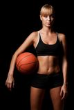 Woman standing with basketball Royalty Free Stock Image