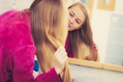 Woman looking at her reflection in mirror. Woman standing in bathroom looking at her reflection in mirror brushing her long blonde hair stock photography