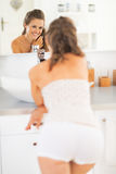 Woman standing in bathroom and looking in mirror Stock Photos