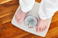 Woman standing on bathroom scale. Woman (only feet to be seen) standing on bathroom scale measuring her weight controlling her dieting results royalty free stock images