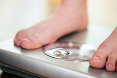 Woman standing on bathroom scale. Woman (only feet to be seen) standing on bathroom scale measuring her weight controlling her dieting results royalty free stock photography