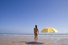 Woman standing at the beach. A summer scenic with a yellow umbrella at the beach royalty free stock images