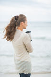 Woman standing on beach with cup of hot beverage Stock Photography