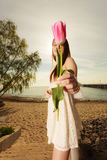 Woman standing on beach giving pink tulip Royalty Free Stock Images
