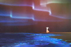 Woman standing on beach glows with Northern lights Aurora borealis above Royalty Free Stock Photography