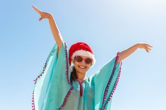 A woman standing on the beach with her hands up to the sky, wearing a Santa Hat royalty free stock image