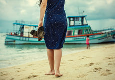 Woman standing on the beach and holding in his hand spanking Royalty Free Stock Images