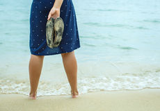 Woman standing on the beach and holding in his hand spanking Stock Image