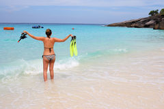 Woman standing at the beach holding snorkel gear Stock Image