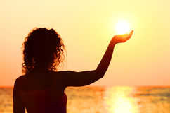 Woman standing on beach, holding sun in hand Stock Photo