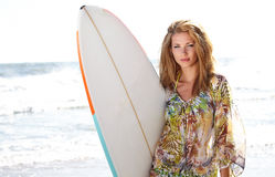 Woman standing on the beach holding a surfboard Royalty Free Stock Photo