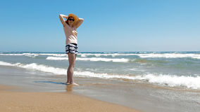 Woman is standing at the beach with jute hat on Stock Image