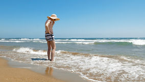 Woman is standing at the beach with jute hat on Royalty Free Stock Images