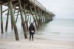 Woman on beach near pier stock images