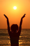 Woman standing on beach, raises hands royalty free stock image