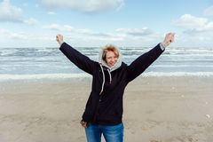 Woman standing on the beach and rising her arms up.  royalty free stock photo