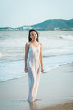 Woman standing on beach in summer. Happy multiracial Asian girl going to sea. Woman standing on beach in summer. Beautiful happy multiracial Asian girl in white Royalty Free Stock Images