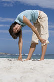 Woman standing on beach, touching toes, smiling, side view, portrait, surface level Stock Image