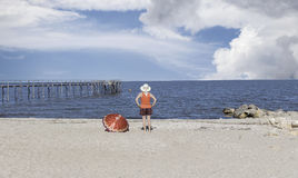 Woman standing on the beach watching children swimming Stock Images