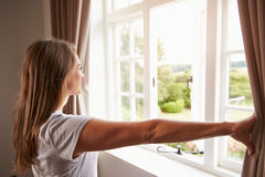 Woman Standing By Bedroom Window And Opening Curtains Royalty Free Stock Image