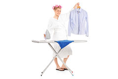 Woman standing behind an ironing board Stock Images
