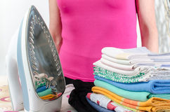 Woman standing behind the ironing board Stock Images