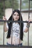 Woman  standing behind of metal garden fencing Stock Image