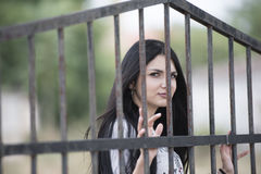 Woman  standing behind of metal garden fencing Royalty Free Stock Photo