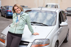 Woman standing behind a new own car. Young pretty Caucasain woman standing behind a new own car Royalty Free Stock Photos