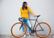 Woman standing with bicycle Stock Image
