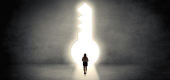 Woman standing in a big keyhole stock images