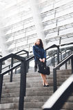 Woman standing on big stairs outdoor and leaning against railings Royalty Free Stock Photo