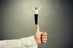 Woman standing on big thumbs up. Happy small woman standing on big thumbs up and raising her hands up over dark grey background stock photos