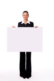 Woman standing beside a blank board. Isolate of a business woman standing beside a blank board royalty free stock photos
