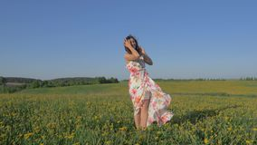 Woman standing in a blooming yellow field in a dress raises arms and turning. Pretty playful caucasian woman on a blooming yellow field in a beauty dress. Raises stock footage