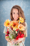 Woman standing on blue background. Emotional cheerful young dark-blonde woman with long hair standing in half length with bright wildflowers on creative Stock Photos