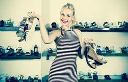 Woman standing in boutique and having many shoes. Cheerful beautiful woman standing in boutique and having many shoes in hands royalty free stock photos