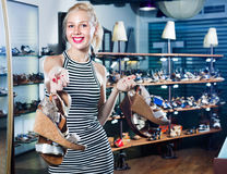 Woman standing in boutique and having many shoes. Happy beautiful young woman standing in boutique and having many shoes in hands stock photography