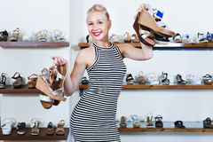 Woman standing in boutique and having many shoes. Positive cheerful woman standing in boutique and having many shoes in hands royalty free stock photography