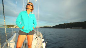Woman standing on bow of sailing boat enjoying view of sea stock video footage