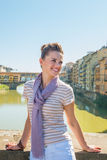 Woman standing on bridge overlooking ponte vecchio Royalty Free Stock Photo