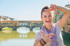 Woman standing on bridge overlooking ponte vecchio Royalty Free Stock Image