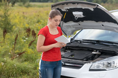 Woman standing at broken car in meadow and reading owner manual Stock Photos